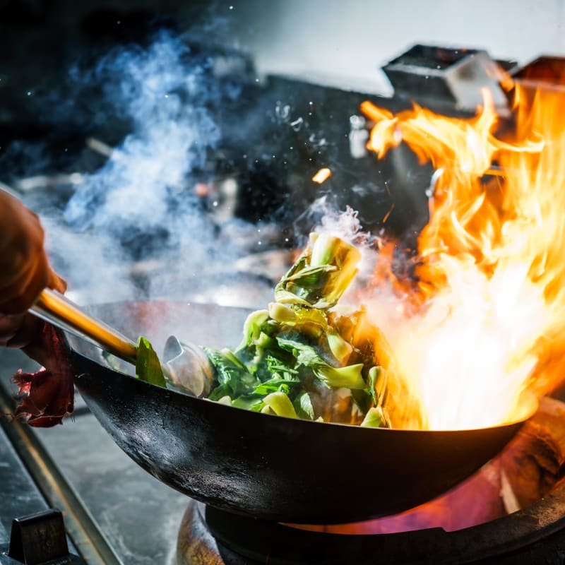 Chef cooking fresh vegetables in a wok at one of the seaside restaurants at Portside Ventura Harbor in Ventura, California