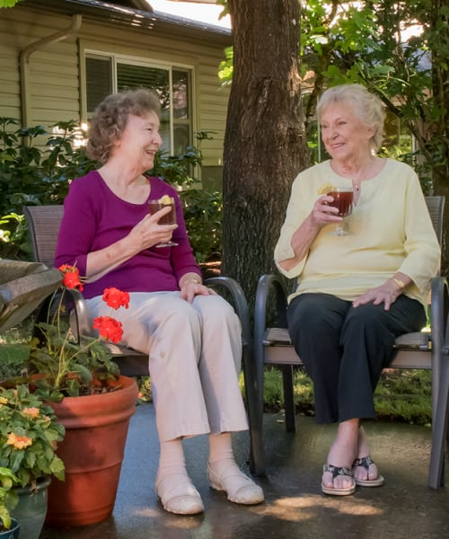 Two residents drinking tea in the gardens at The Springs at Wilsonville in Wilsonville, Oregon
