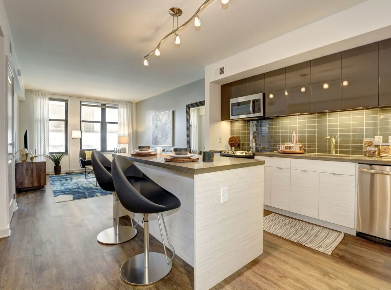 A kitchen with an island bar at Solaire 7077 Woodmont in Bethesda, Maryland