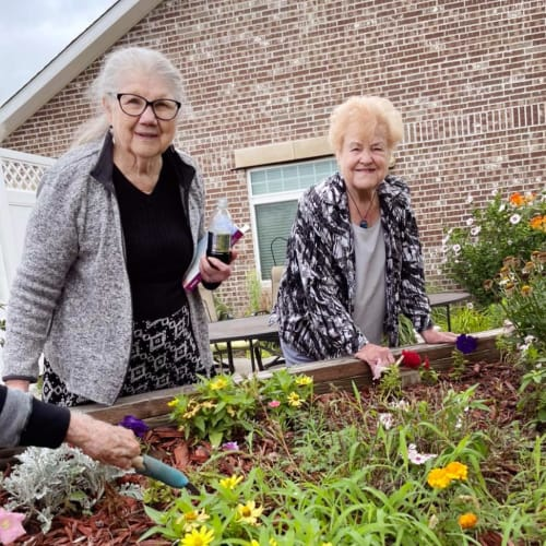 Residents outside watering plants at Oxford Glen Memory Care at Owasso in Owasso, Oklahoma