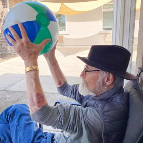 Resident playing with a ball at Oxford Glen Memory Care at Sachse in Sachse, Texas