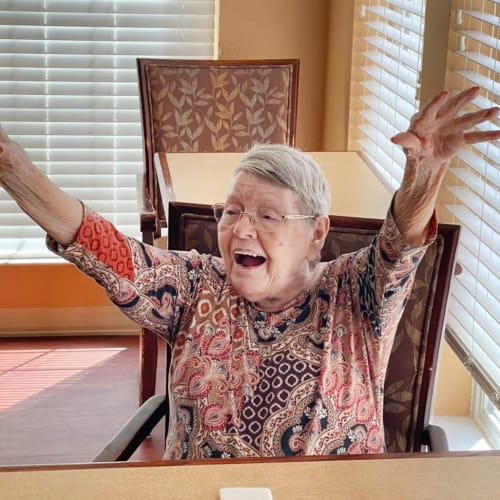 A resident with stretched out arms at Oxford Glen Memory Care at Sachse in Sachse, Texas