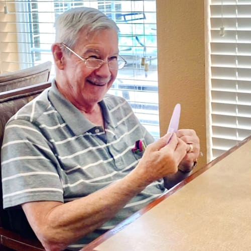 Smiling resident crafting at Oxford Glen Memory Care at Sachse in Sachse, Texas
