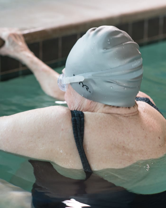 Resident swimming in heated indoor pool at The Springs at Tanasbourne in Hillsboro, Oregon.