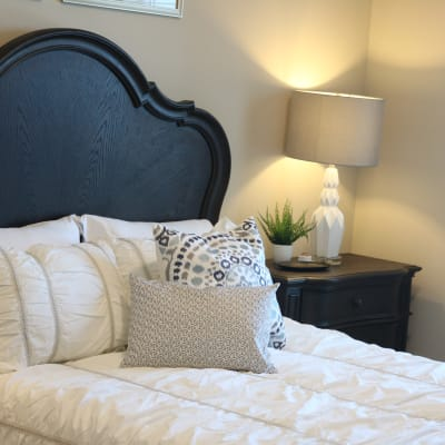 Modern bedroom with night stand and soft lighting at The Sanctuary at Brooklyn Center in Brooklyn Center, Minnesota