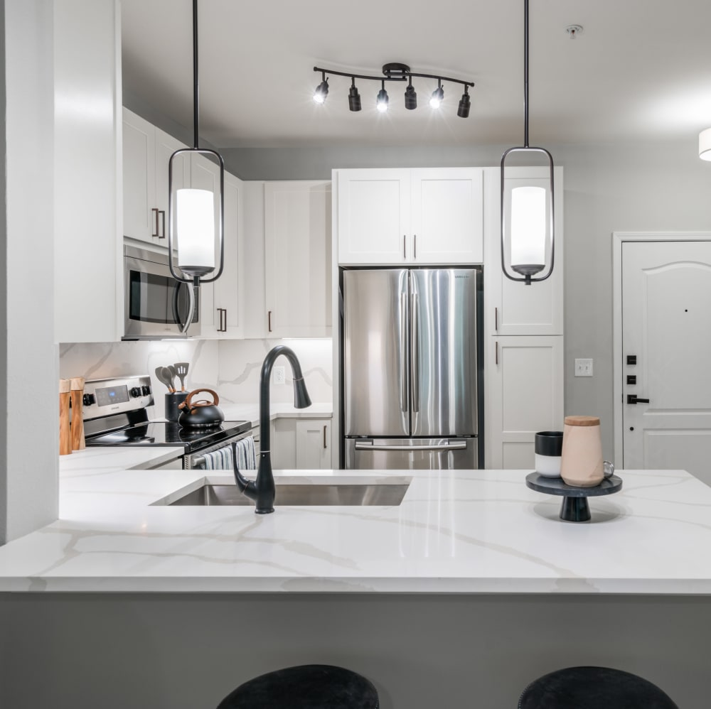 Beautiful kitchen with stainless-steel appliances and white cabinetry at The JaXon in Kingwood, Texas
