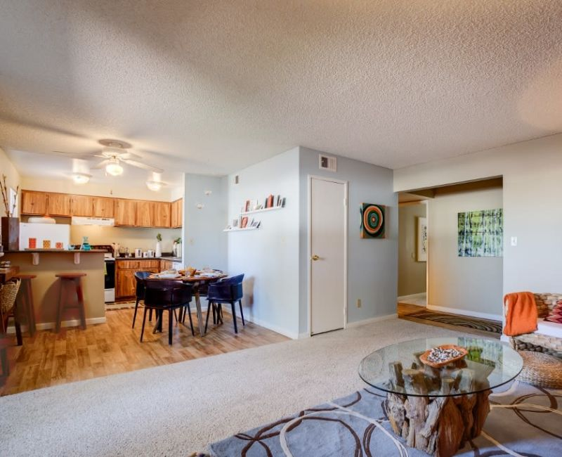 Well-decorated living area with looking into the kitchen area of an open-concept floor plan of a model home at 505 West Apartment Homes in Tempe, Arizona
