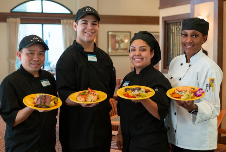 Dining team holding executive chef meals