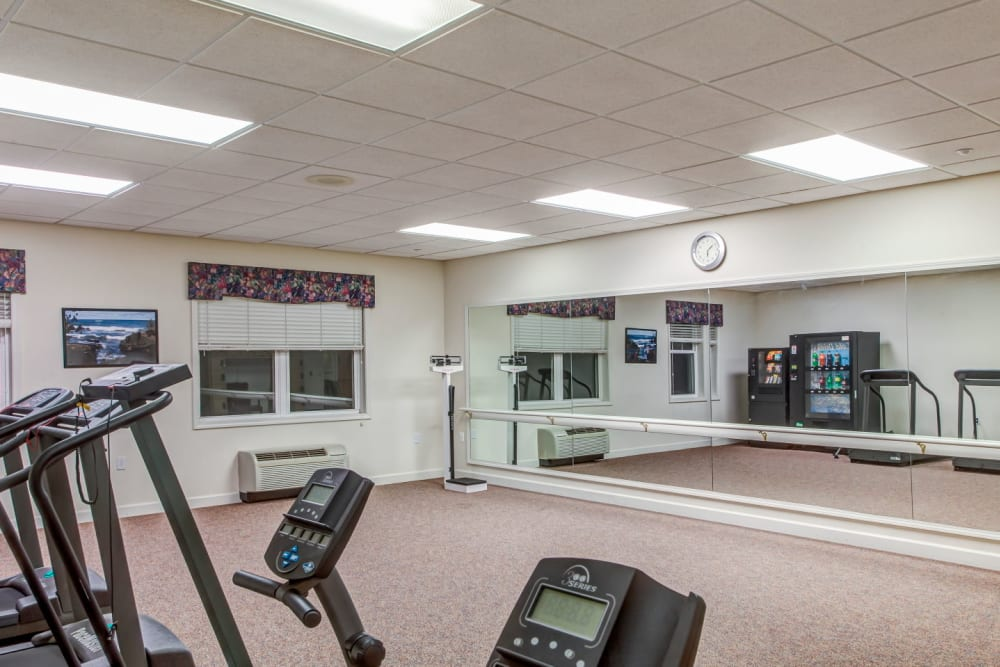 Deluxe exercise studio with machines and mirror at Grand Victorian of Sycamore in Sycamore, Illinois
