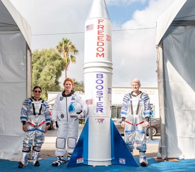 The Bankers Hill team poses in front of the custom rocket with their astronaut uniforms on.