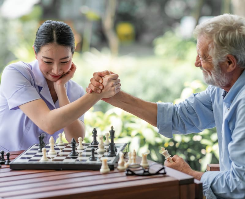 Staff member and resident playing chess at Arbor Glen Senior Living in Lake Elmo, Minnesota