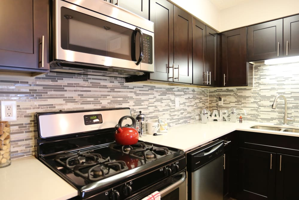 An apartment kitchen with a tile backsplash at Fox and Hounds Apartments in Columbus, Ohio