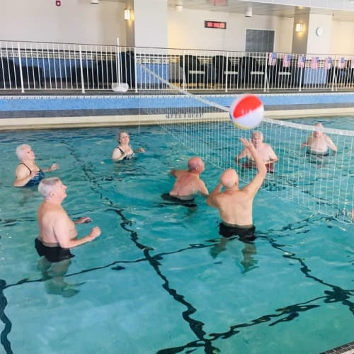 Residents playing pool volleyball in the indoor heated swimming pool at The Chamberlin in Hampton, Virginia