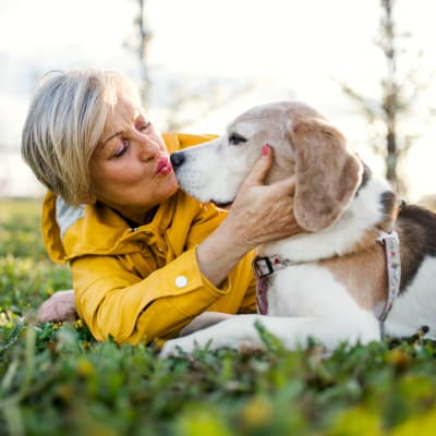 A woman and her dog lay in the grass at Northglenn Heights Assisted Living in Northglenn, Colorado