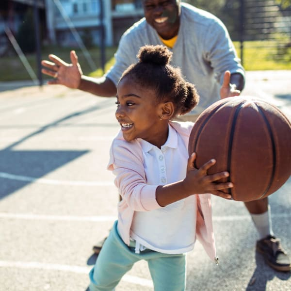 Resident playing basketball with their kid at Palmetto Greens Apartment Homes in Covington, Louisiana