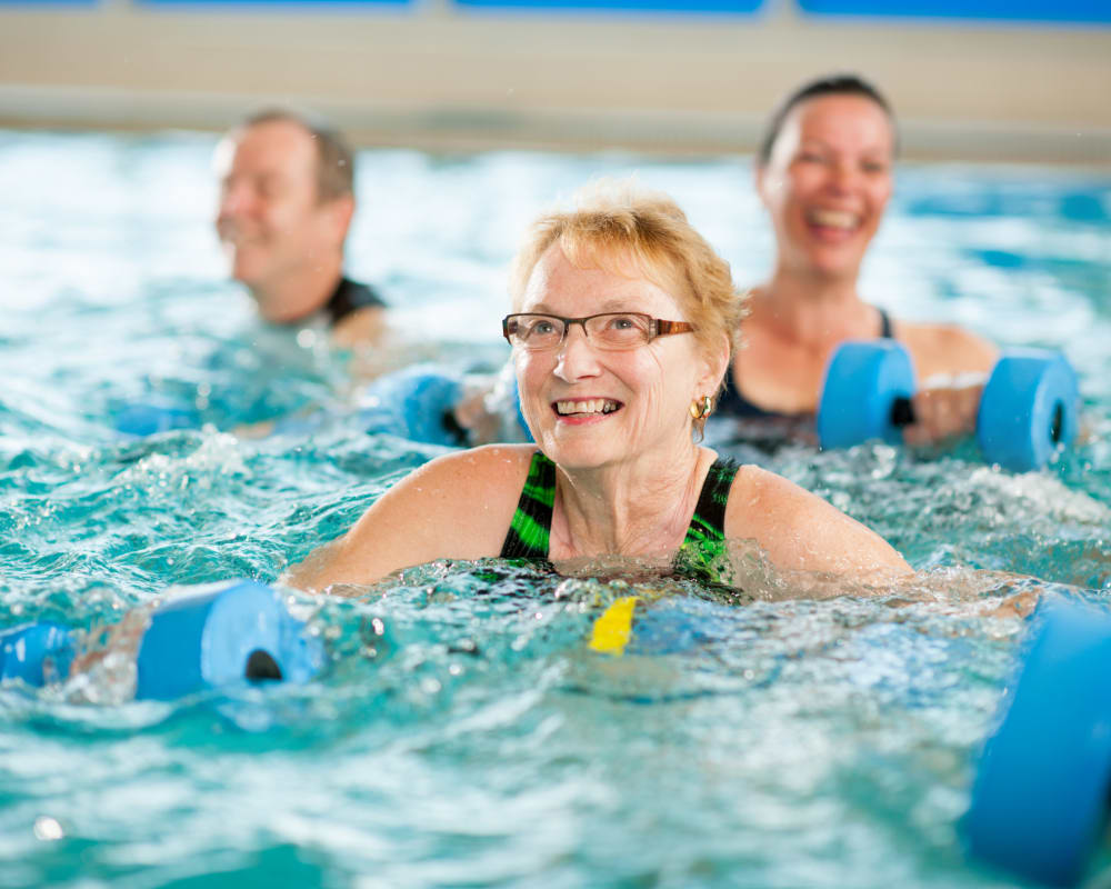 Residents taking a fitness class in the indoor swimming pool at WellQuest of Elk Grove in Elk Grove, California