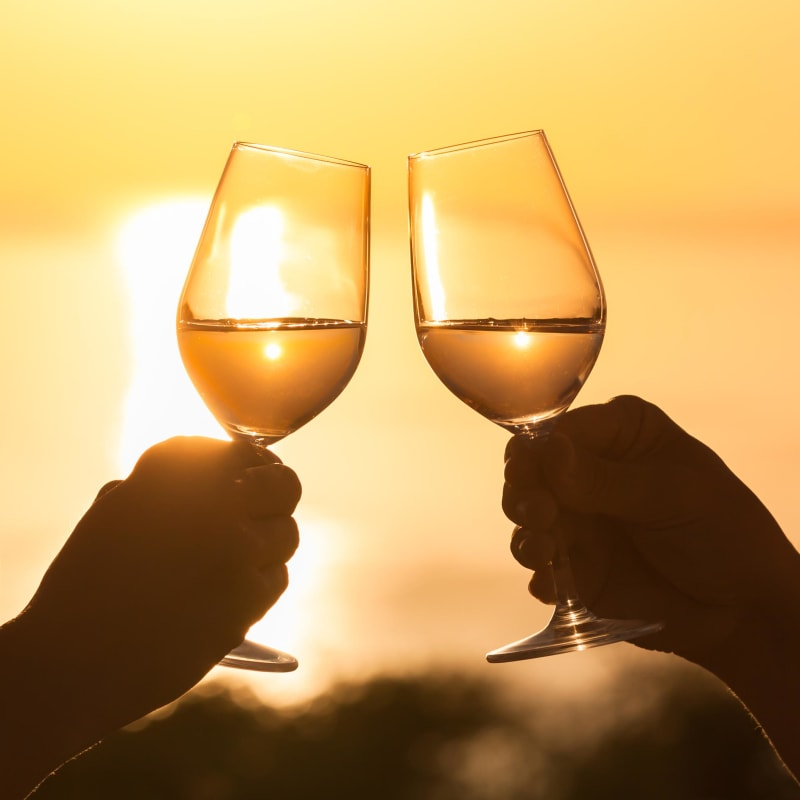 Couple toasting the good life at sunset at Portside Ventura Harbor in Ventura, California