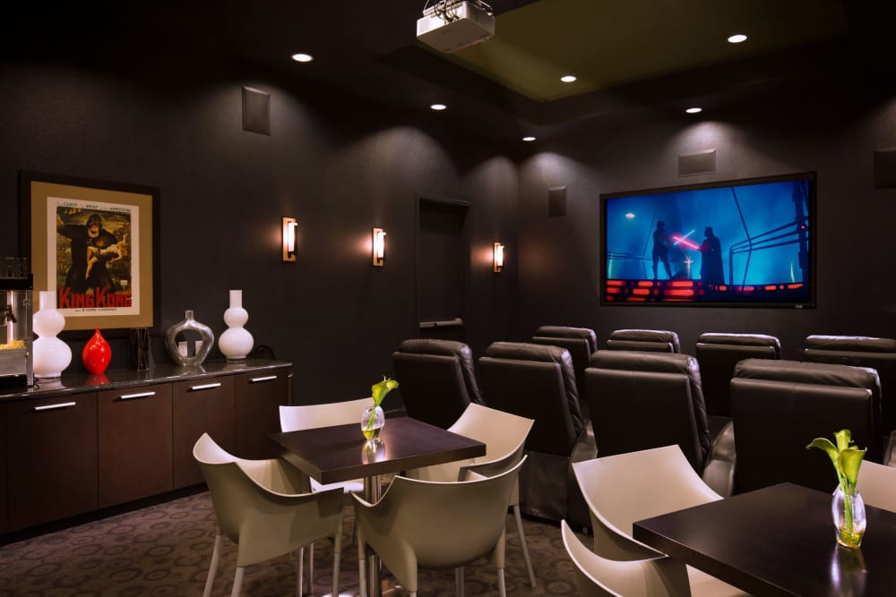 Large theater with table and chairs for eating while watching a movie at Venu at Galleria Condominium Rentals in Roseville, California