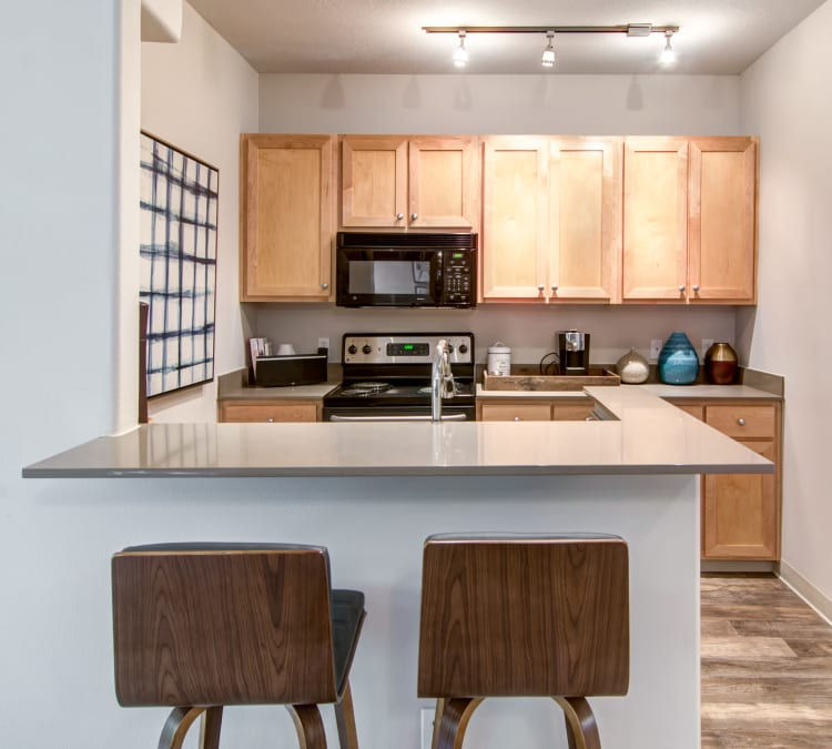 Quartz countertop and stainless-steel appliances in a model home's kitchen at Sofi at Forest Heights in Portland, Oregon