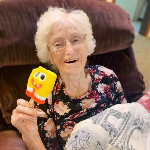 A resident eating an ice cream at Oxford Glen Memory Care at Owasso in Owasso, Oklahoma