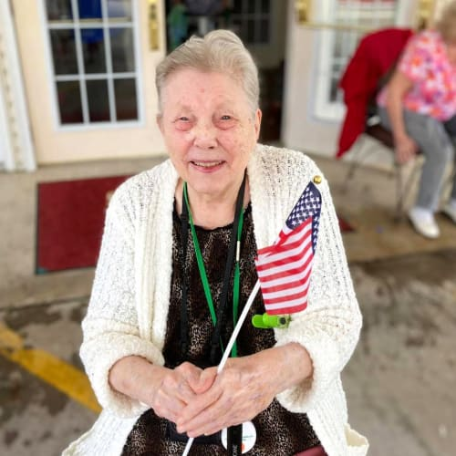 Smiling resident with flag at Canoe Brook Assisted Living in Broken Arrow, Oklahoma