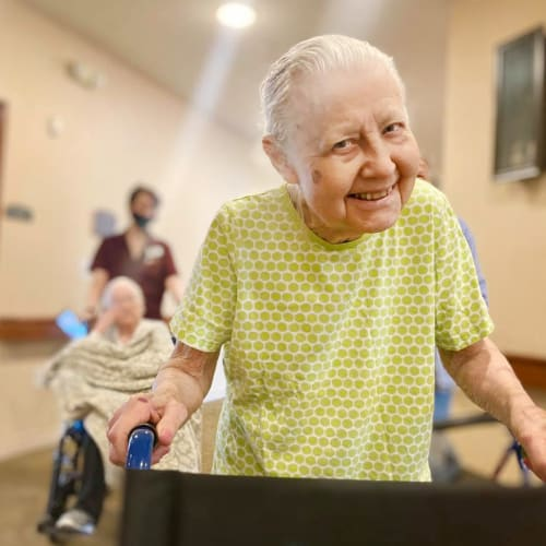 Resident walking and smiling at Oxford Glen Memory Care at Carrollton in Carrollton, Texas