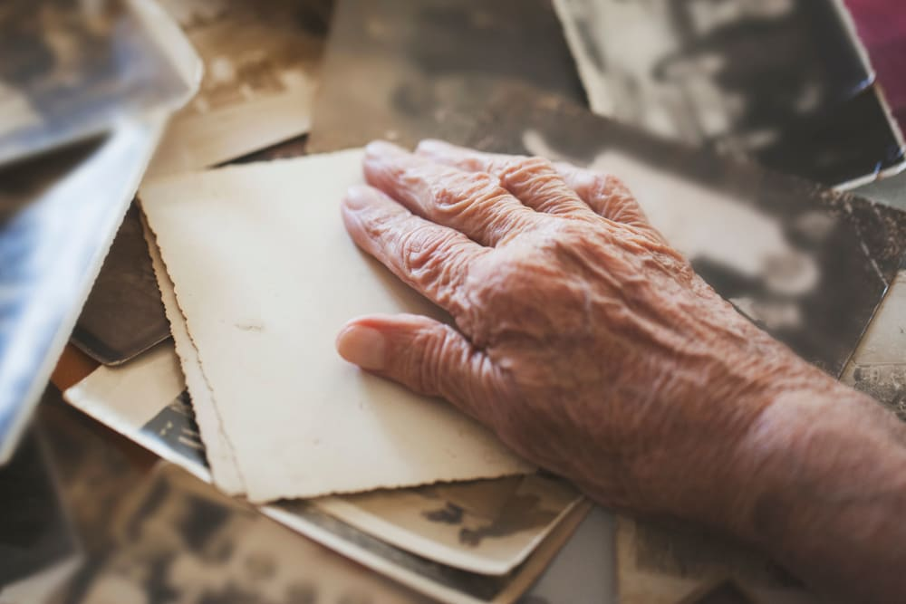 A resident's hand and collection of old photographs at Westminster Memory Care in Lexington, South Carolina