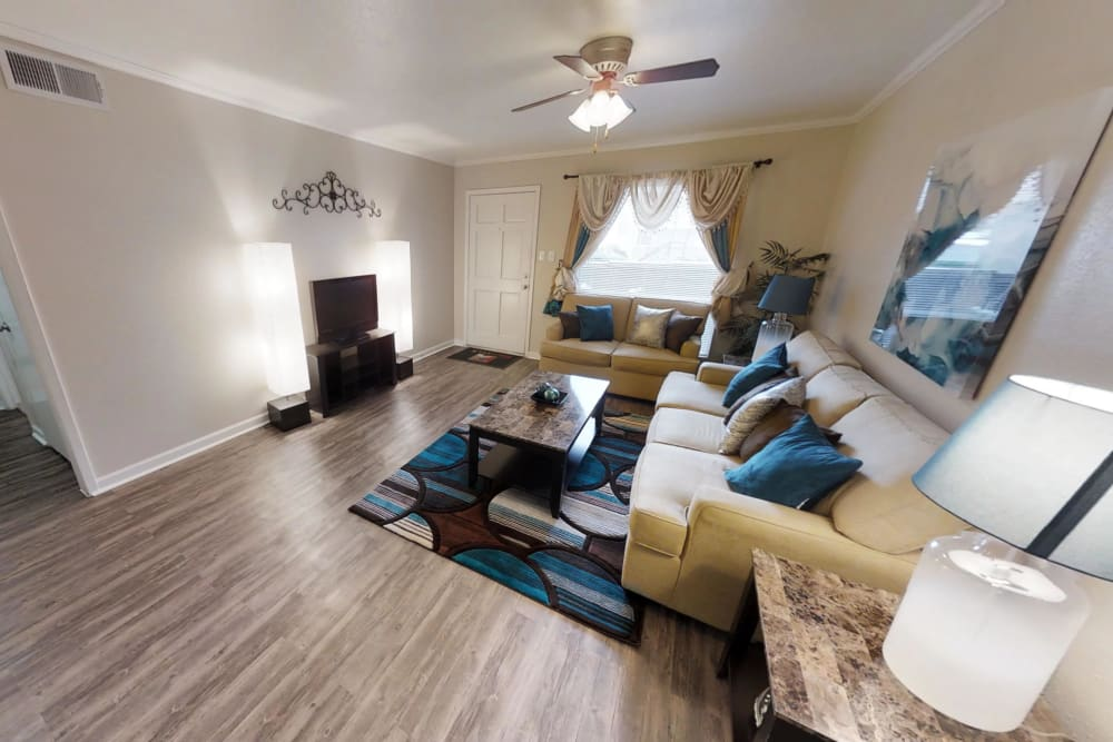 Living room with wood-style flooring at Falls of Maplewood Apartments in Houston, Texas