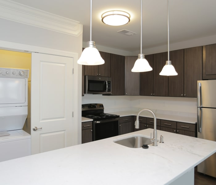 Open gourmet kitchen with adjacent washer and dryer in model home at Aqua on 25th in Virginia Beach, VA