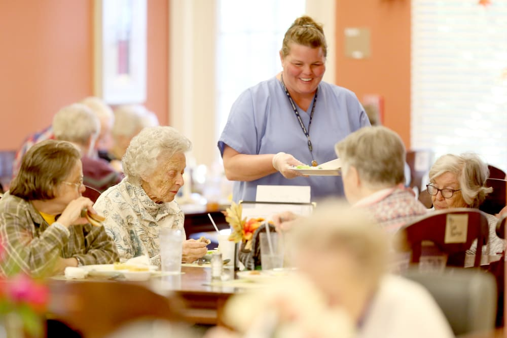 A staff member helping with dinner at Providence Assisted Living.