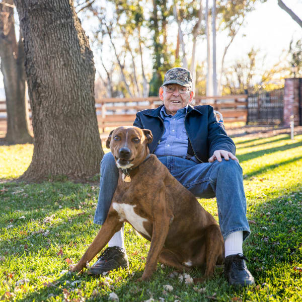 A man outside with his dog at Pacifica Senior Living Sterling in Sterling, Virginia