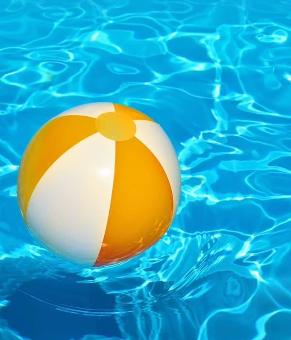 Beach ball floating in Eagle Rock Apartments at Freehold's swimming pool in Freehold, New Jersey