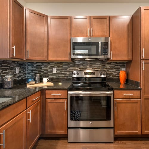Gourmet kitchen with a subway tile backsplash in a model home at Olympus Waterford in Keller, Texas