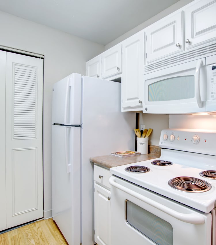 Kitchen with hardwood flooring and a pantry for additional storage in a model home at Waterstone Fremont in Fremont, California