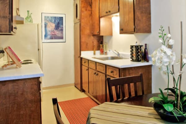 Kitchen and dining room with wood cabinets at 7th Street Manor in Chico, California