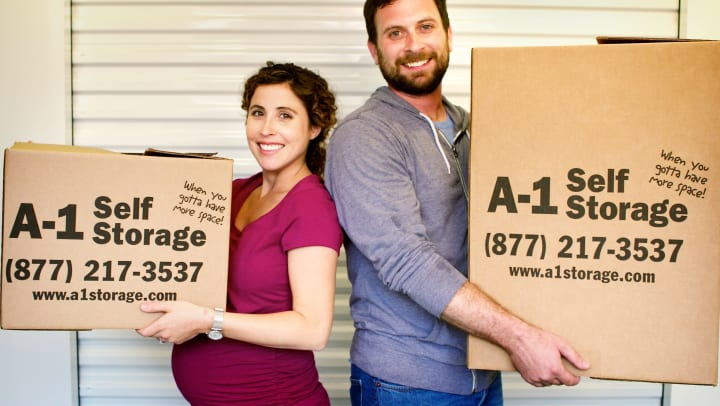 young couple holding boxes in front of storage unit door