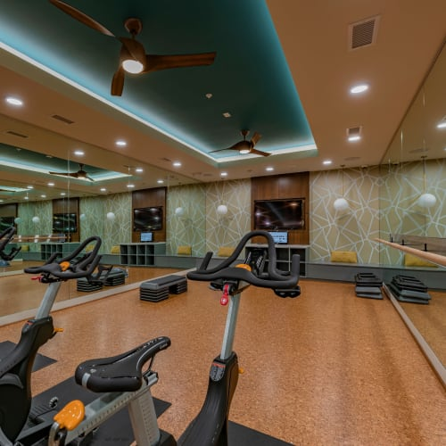 Modern fitness center with a flat-screen TV for workouts at Encore Tessera in Phoenix, Arizona