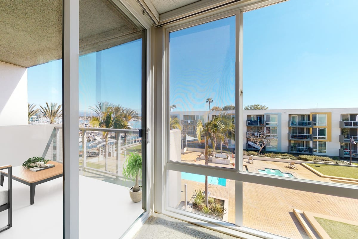 Floor-to-celing window and balcony with views of the marina at Waters Edge at Marina Harbor in Marina del Rey, California