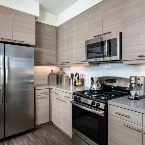 Gourmet kitchen with stainless-steel appliances and quartz countertops in a model apartment at Fusion Apartments in Irvine, California