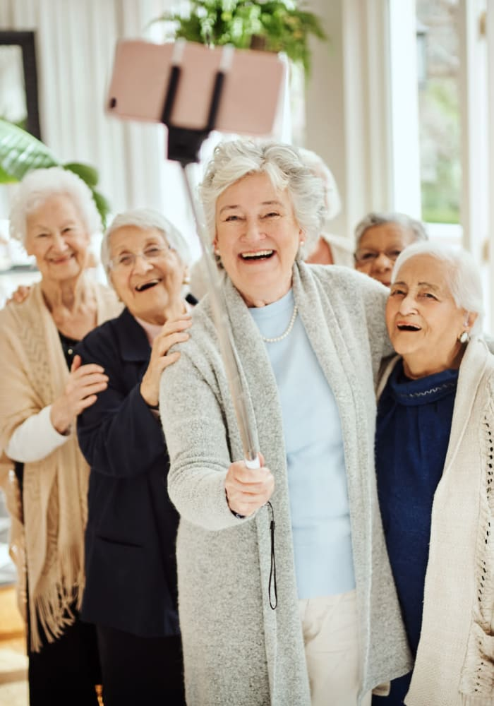 Residents smiling and taking pictures using a selfie stick at Northglenn Heights Assisted Living in Northglenn, Colorado