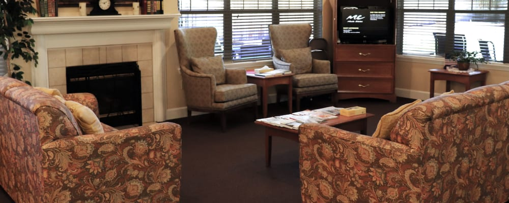 Sitting area with comfy armchairs, fireplace, television set in upscale senior living facility at The Springs at Willowcreek in Salem, Oregon