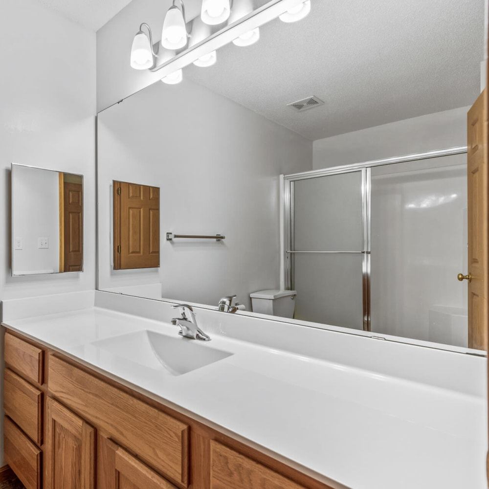 Tiled shower and a large vanity mirror in a model townhome's bathroom at Oaks Lincoln Apartments & Townhomes in Edina, Minnesota