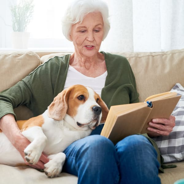Woman with dog reading a book at Pacifica Senior Living Sterling in Sterling, Virginia