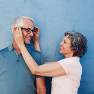 Resident putting glasses on her partners face at Sunstone Village in Denton, Texas