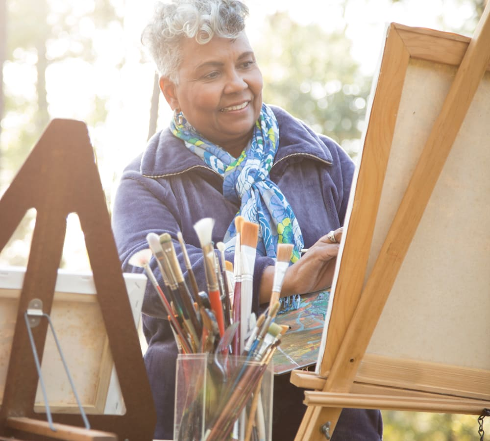 Resident painting a picture on an easel at Kingston Bay Senior Living in Fresno, California