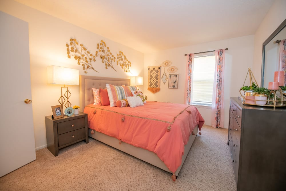 Bright bedroom with window at Riverpark Apartments in Tulsa, Oklahoma