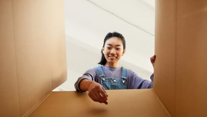 Woman reaching into cardboard box and smiling