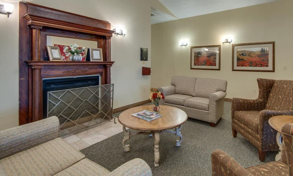 Cozy seating area with a fireplace at Victorian Place of Washington Senior Living in Washington, Missouri