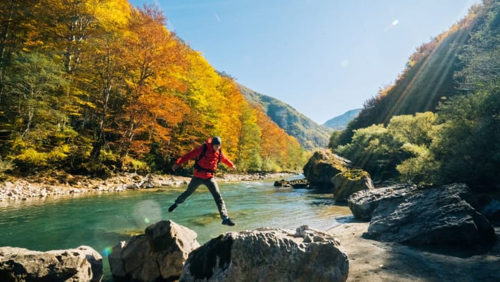 Man jumps between rocks at a river with fall colors in the background