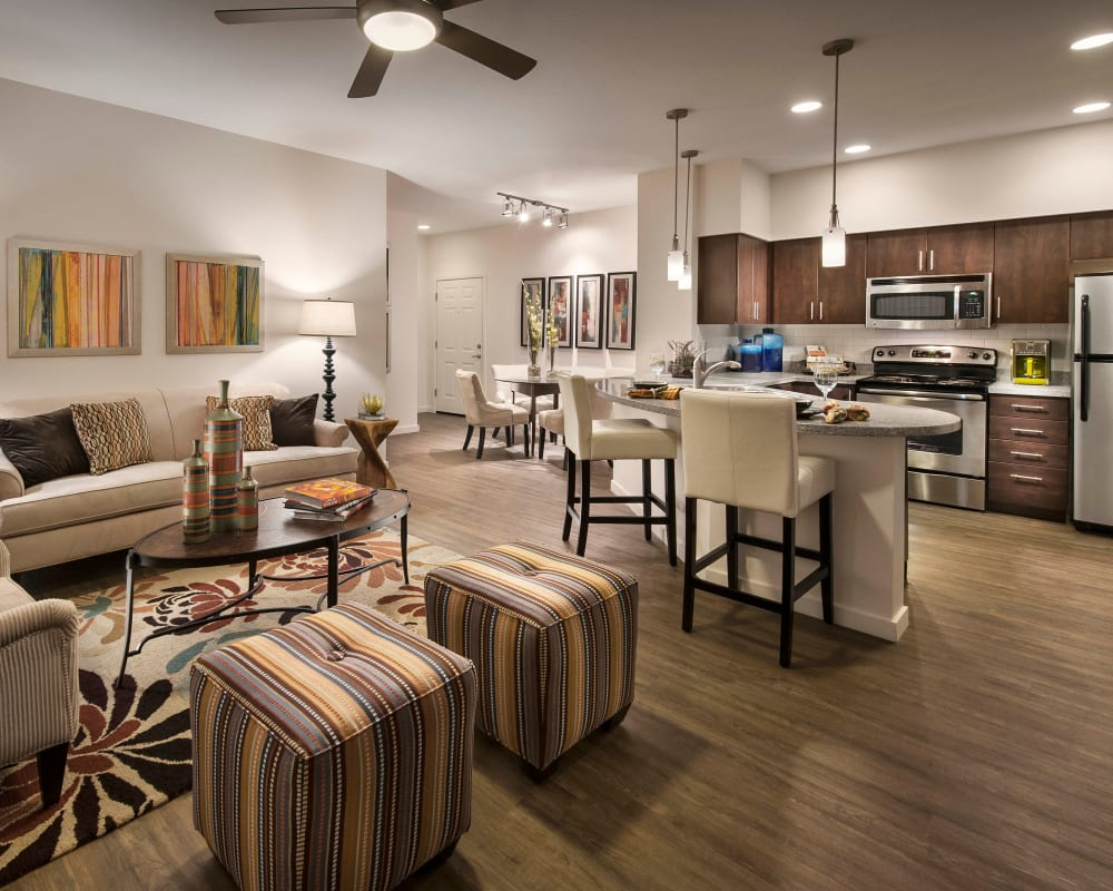 Large open-concept living area with hardwood flooring and a ceiling fan in a model home at Redstone at SanTan Village in Gilbert, Arizona